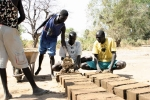 Former child soldiers making bricks to build a school
